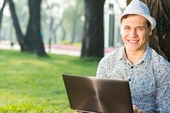 Young man working in the park with a laptop Stock Images