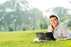 Young man working in the park with a laptop Royalty Free Stock Images