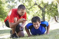 Young Man Working With Personal Trainer In Park Stock Photo