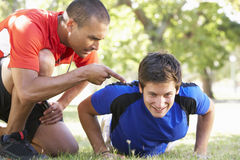 Young Man Working With Personal Trainer In Park Stock Image