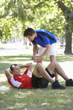 Young Man Working With Personal Trainer In Park Stock Photos