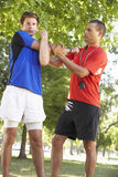 Young Man Working With Personal Trainer In Park Royalty Free Stock Photo