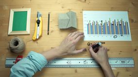 Young man working with printed graphs making notes with marker at wooden desk. Metal ruler, house model, photo frame, yellow paper knife, craft rope at wooden stock footage