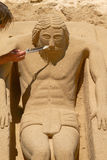Young Man Working on Sand Sculpture of Jesus in Cadiz, Spain Stock Images