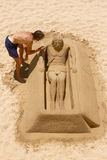 Young Man Working on Sand Sculpture of Jesus in Cadiz, Spain Royalty Free Stock Photography