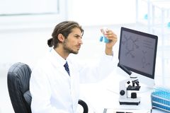 Scientist in the chemical lab examines a flask with a substance. A young man working in a scientific laboratory, collecting a flask Royalty Free Stock Photo