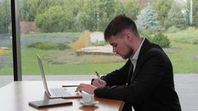 Young man working with securities at a table in a cafe. Young man in a black suit and white shirt sitting alone at a table in a suburban cafe, side view, working stock video