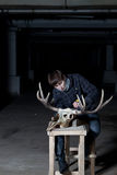 Young man working with sharp deer skull in dark basement Stock Photo
