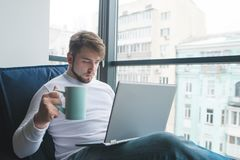 A young man is working on a sofa for a laptop with a cup of hot drink. Royalty Free Stock Images