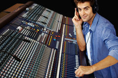 Young man working on sound mixer console Stock Image