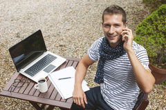 Young man working talking with smart phone in outdoors. Royalty Free Stock Photo