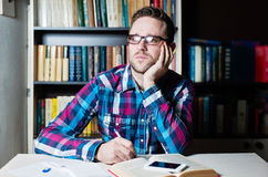 Young man working and thinking in the library. Young man in casual cloth and glasses working and thinking in the library Stock Photos