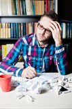 Young man working and thinking in the workplace. Young man in casual cloth and glasses working and thinking in the workplace Royalty Free Stock Image