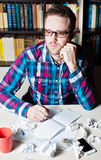 Young man working and thinking in the workplace. Young man in casual cloth and glasses working and thinking in the workplace with cup of tea or coffee Royalty Free Stock Images