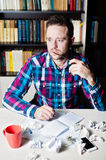 Young man working and thinking in the workplace. Young man in casual cloth and glasses in hand working and thinking in the workplace with cup of tea or coffee Royalty Free Stock Image