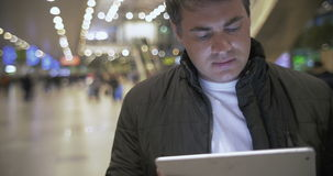 Young man working with touch pad at the airport. Young man in jacket using tablet computer at the crowded airport. Easy work with portable device stock footage