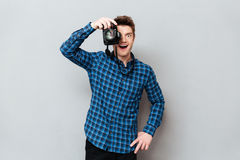 Young man working wih camera. Young joyful man working wih camera over grey stock photo