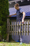 Young man working on a wooden fence. In the garden alongside his house hammering the upright post with a mallet in a property and yard maintenance concept Royalty Free Stock Images