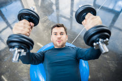 Young man workout with dumbbells on fitness ball at gym. Handsome young man workout with dumbbells on fitness ball at gym Stock Image