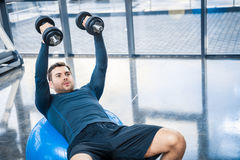 Young man workout with dumbbells on fitness ball at gym. Handsome young man workout with dumbbells on fitness ball at gym Stock Photo