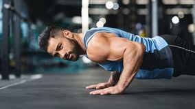 Strong caucasian guy making plank or push ups exercise,. Young man workout in fitness club. Profile portrait of strong caucasian guy making plank or push ups stock photography