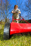 Spring mowing. A young man works in the garden and mows the grass on a sunny spring day stock photography