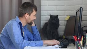 A young man works at home and talking on the phone, in the background a funny cat