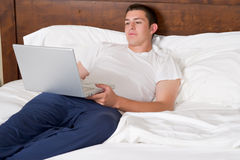 Young man works on laptop in bed Stock Photos