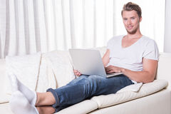 Young man works with laptop on couch Stock Photo