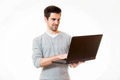 A young man works on a laptop while standing Stock Photography