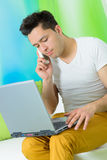 Young man works with laptop and talk at telephone Royalty Free Stock Image