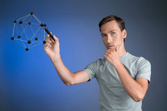 Young man works on a model of molecule. Stock Images