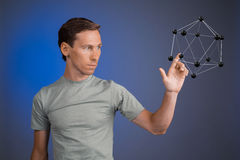 Young man works on a model of molecule. Stock Photos