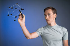 Young man works on a model of molecule. Stock Image