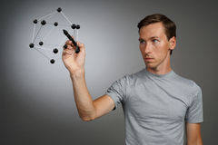 Young man works with a model of molecule. Royalty Free Stock Photos