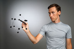 Young man works with a model of molecule. Stock Images