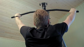 Young man works out on his home gym equipment to exercise his shouloder muscles stock video