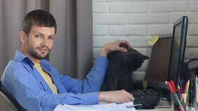 A young man works remotely at home, stroking a cat and looked into the frame