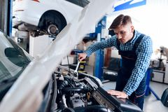 A young man works at a service station. The mechanic is engaged in repairing the car. royalty free stock photo