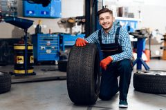 A young man works at a service station. The mechanic is engaged in repairing the car. A young mechanic posing with tires from the car Stock Photos