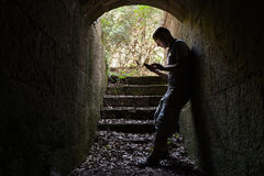 Young man works on a smart-phone in dark tunnel Royalty Free Stock Images