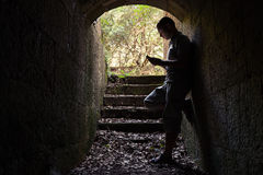 Young man works on a smartphone in dark tunnel Royalty Free Stock Images