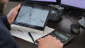 Young man works, using tablet and calculator in leading company. Specialist holds silver gadget in hand, screen shows technical diagrams and counts using stock video footage