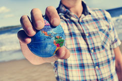 Young man with a world globe in his hand stock image