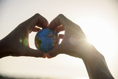 Young man with a world globe in his hands stock photography