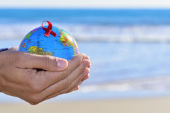 Young man with a world globe with a red ribbon Stock Photography