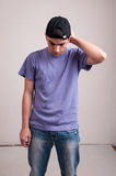 Young man in worry on dirty background in studio Stock Photo