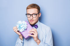 Young man with a wrapped gift box. Present, birthday, Valentine. Studio portrait over blue background Royalty Free Stock Photo