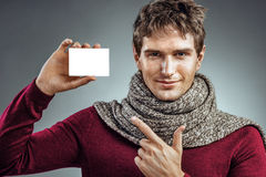 Young man wrapped in scarf, holding box for medicine. Royalty Free Stock Photo