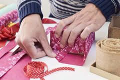 Young man wrapping a gift Stock Images